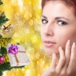 Beautiful portrait young Caucasian Women over golden abstract Christmas background with holidays Tree — Stock Photo #60573839