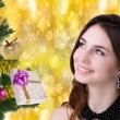 Beautiful portrait young Caucasian Women over golden abstract Christmas background with holidays Tree — Stock Photo #60573843