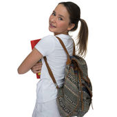 Young schoolgirl carrying a book and backpack — Stock Photo