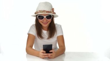 Trendy young teenager smiling as she reads an sms — Stock video