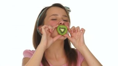 Young girl biting on a slice of fresh kiwifruit — Stok video