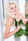 Stunning young blond woman with roses — Stock Photo