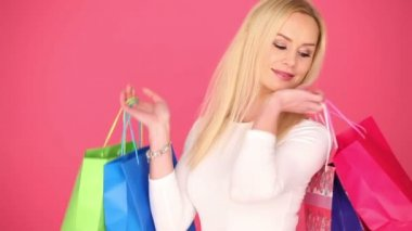 Happy young shopaholic carrying her bags — Wideo stockowe