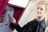 Smiling Woman Inserting a Card in an ATM — Stock Photo