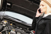 Young woman calling roadside assistance — Stock Photo