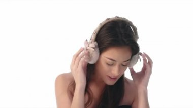 Beauty woman expression on white 4k video wearing winter ear warmers — Stockvideo