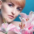 Gorgeous woman with a bunch of pink lilies — Stock Photo #69505855