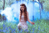 Artistic portrait of a girl in a bluebell forest — Stock Photo