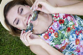 Happy Woman Holding Shades While Lying on Grasses — Stock Photo