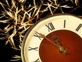Eve of new year.Clock face and golden firework. — Stock Photo