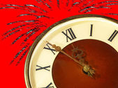 Dial of hours and fireworks on red background.Eve of new year. — Stock Photo