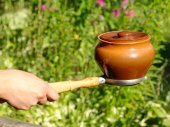 духовку вилкой и глины горшок в руке женщина. — Стоковое фото