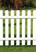 White fence on green grass. — Stock Photo