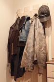 Various clothes hanging on coat rack. — Photo