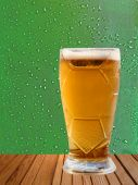 Beer glass on wooden surface against drips abstract background. — Stock Photo