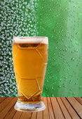 Beer glass against ice crystals and drips green background. — Zdjęcie stockowe
