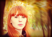 Pretty red hair girl looks at camera.Soft bokeh. — Stock Photo
