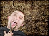 Mad man with scissors cuts off itself tongue on grunge backgroun — Stock Photo