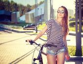 Trendiga hipster flicka med cykel i staden — Stockfoto
