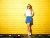 Hipster móda dívka v žluté zdi — Stock fotografie