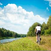 Cyclist Riding a Bike on River Bank — Stok fotoğraf
