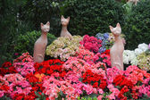 Statue of three cats with flowers — Stock Photo