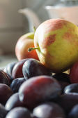 Plums and apples - autumnal fruits on the kitchen — Stock Photo