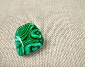 Polished malachite stone on canvas background — Stock Photo