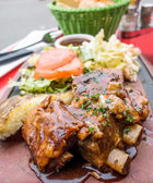 Grilled meat ribs on the plate with hot sauce  — Stock Photo
