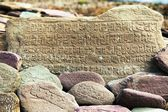 Mani wall and stones with buddhist symbols — Стоковое фото