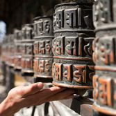 Prayer wheels and a hand  — Stock Photo