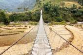 Rope hanging suspension bridge in Nepal with paddyfield and tourist  — Stock Photo