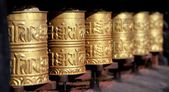 Golden buddhist prayer wheels — Stock Photo