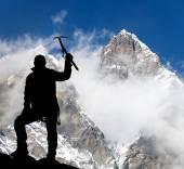 Mount Lhotse and silhouette of man wirh ice axe — Stock Photo