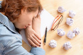 Tired woman thinking and writing paper — Stock Photo