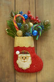 Christmas stocking with fir branches, berries and candy canes — Stock Photo