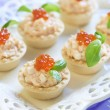 Tartlets with seafood salad, red caviar and basil — Stock Photo #53175529