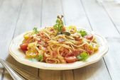 Pasta with tomatoes, ham, capers and cheese — Stock Photo