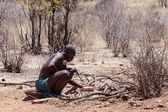 Himba man adjusts wooden souvenirs in fireplace for tourists — Stockfoto