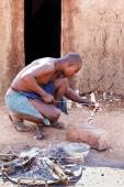 Himba man adjusts wooden souvenirs in fireplace for tourists — Stock Photo
