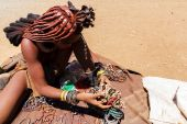 Himba girl with souvenirs for sale in traditional village — Stock Photo