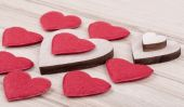 Valentine's fabric and wooden hearts on a wooden background — Stock Photo