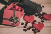 Bottle of vine, red hearts and small present a retro style — Stock Photo