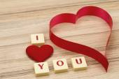 Valentine's paper hearts on a wooden background and tex i love you — Stock Photo