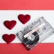 Audio cassette tape on red backgound with fabric heart — Stock Photo #65140919