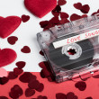 Audio cassette tape on red backgound with fabric heart — Stock Photo #65140943