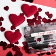 Audio cassette tape on red backgound with fabric heart — Stock Photo #69681881