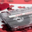 Audio cassette tape on red backgound with fabric heart — Stock Photo #69681883