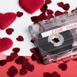 Audio cassette tape on red backgound with fabric heart — Stock Photo #69681889