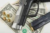 Gun with bullet on US dollar banknotes — Stockfoto